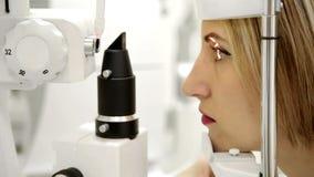El oftalmólogo comprueba los ojos de la mujer almacen de video