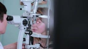 El oftalmólogo comprueba los ojos de la mujer metrajes