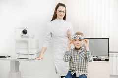 El oftalmólogo pediátrico del doctor comprueba la visión del muchacho del niño Selección del concepto de lentes de los vidrios fotografía de archivo libre de regalías