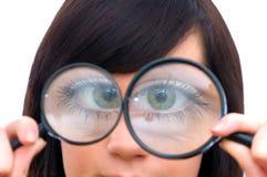 El ojo de la muchacha magnificó Fotos de archivo