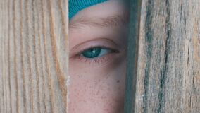 El ojo inusual de la turquesa de un adolescente de rasgones mira por completo a través de la entrada o de una ranura en la cerca  metrajes