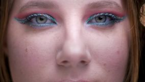 el Ojo-retrato del modelo rubio con maquillaje colorido abre ojos y la observación tranquilamente en cámara en luces borrosas almacen de video