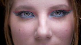 el Ojo-retrato del modelo rubio con maquillaje colorido aumenta ojos y los relojes en cámara en fondo borroso de las luces metrajes