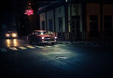 El oldtimer rojo oscuro pasa cruces en la noche debajo de la farola Imagen de archivo libre de regalías