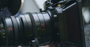 El operador da vuelta al anillo del foco en la lente con una caja mate almacen de metraje de vídeo