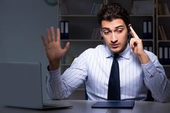 El operador de centro de atención telefónica que habla con el cliente durante turno de noche fotografía de archivo