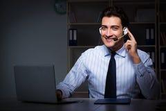 El operador de centro de atención telefónica que habla con el cliente durante turno de noche imagen de archivo