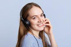 El operador de sexo femenino sonriente con los auriculares felices de oír al cliente, explica algo con la expresión positiva, le  Fotos de archivo libres de regalías