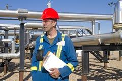El operador de sexo masculino del yacimiento de gas revisa el sitio del compresor Imagenes de archivo
