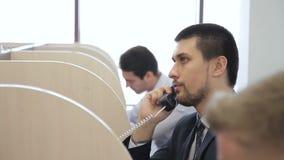 El operador de sexo masculino hace llamada de teléfono mientras que se sienta en oficina moderna almacen de video
