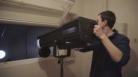 El operador del proyector comprueba el punto del siguiente antes del estroboscópico del concierto, color del cambio metrajes