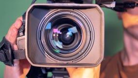 El operador está sosteniendo una cámara de vídeo, dándole vuelta que está enfocando después de eso hacia fuera almacen de video