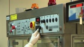 El operador incorpora datos al transportador automático para la producción de drogas metrajes