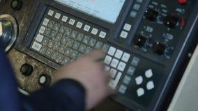 El operador presiona el botón en el primer de la máquina del CNC almacen de video