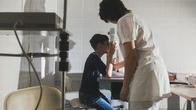 El optometrista de la mujer que examina el ` s del muchacho pre adolescente observa en clínica de la oftalmología Imagen de archivo