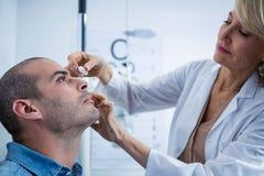 El optometrista que pone descensos en pacientes observa Fotografía de archivo libre de regalías