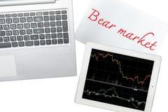 El ordenador, el papel con el texto del mercado bajista y la tableta con el gráfico es i Foto de archivo