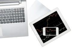 El ordenador, el papel, el smartphone y la tableta con el gráfico se aísla encendido Imagen de archivo