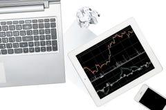 El ordenador, el smartphone, la tableta con el gráfico y el papel se aísla encendido Foto de archivo libre de regalías