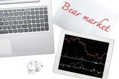 El ordenador, la tableta con el gráfico y el papel con el mercado bajista es isolat Imagenes de archivo