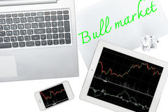 El ordenador, la tableta, el smartphone y el papel con el mercado alcista del texto es Imagen de archivo libre de regalías