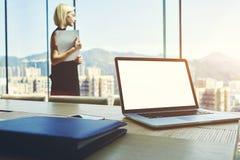 El ordenador portátil abierto con mofa encima de la pantalla del espacio de la copia para su contenido está mintiendo en una tabl imagen de archivo libre de regalías