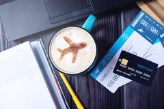El ordenador portátil, billetes de avión, café, tarjeta de crédito miente en la tabla Fotografía de archivo libre de regalías