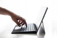 El ordenador portátil compacto expuso la mano pura del fondo de las llaves y el finger blancos de los fingeres que empujaban en l foto de archivo