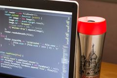 El ordenador portátil con código y rojo programados del web capsuló el frasco a un lado Foto de archivo