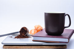 El ordenador portátil, el café, la fruta y el diario comienzan el día Foto de archivo libre de regalías