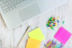 El ordenador portátil en el escritorio de madera blanco con empuje fija los clips de papel Foto de archivo libre de regalías