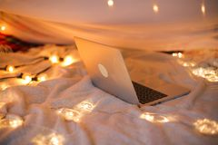 El ordenador portátil miente en la cama en el fondo de una luz del árbol de navidad, movimiento liso Imágenes de archivo libres de regalías