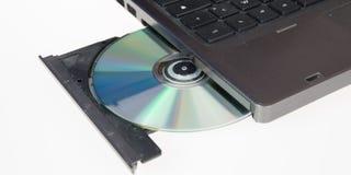 el ordenador portátil se carga con una bandeja abierta del CD-ROM de la impulsión del DVD en un blanco Imagen de archivo libre de regalías