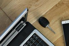 El ordenador portátil, el teléfono elegante la llave del coche y los suelos de parqué imagen de archivo libre de regalías