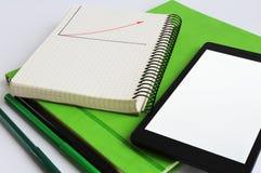 el ordenador portátil y el cuaderno están en un semanario verde Cerca están los marcadores de colores verdes y negros foto de archivo