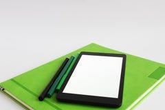 El ordenador portátil y los marcadores están en el semanario verde fotos de archivo libres de regalías
