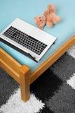 El ordenador portátil y un peluche refieren la cama Foto de archivo libre de regalías