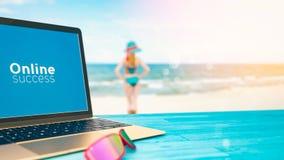 El ordenador se fija en una tabla con una opinión del mar Imagenes de archivo
