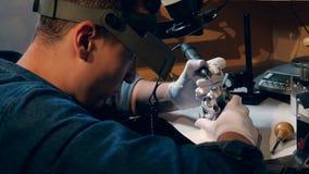 El orfebre está procesando un anillo con una joya Joyería de Working del joyero almacen de video