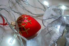 El ornamento en forma de corazón rojo de la Navidad rodeado por chrismas se enciende en superficie de mármol neutral Imágenes de archivo libres de regalías