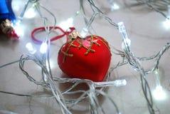 El ornamento en forma de corazón rojo de la Navidad rodeado por chrismas se enciende en superficie de mármol neutral Fotografía de archivo