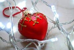 El ornamento en forma de corazón rojo de la Navidad rodeado por chrismas se enciende en superficie de mármol neutral Imagen de archivo libre de regalías