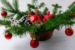 El ornamento rojo de la Navidad adornó la pieza central en cesta de mimbre Fotos de archivo libres de regalías