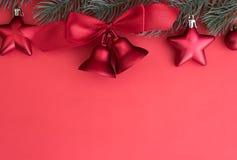 El ornamento rojo de las campanas de la Navidad adorna en árbol de abeto con el backg rojo Imagen de archivo