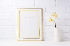 El oro adornó la maqueta del marco con la orquídea amarilla suave en florero Foto de archivo