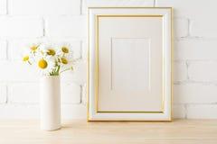 El oro adornó la maqueta del marco con la pared de ladrillo pintada cercana de la margarita Fotos de archivo