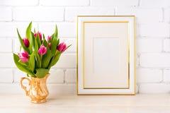 El oro adornó la maqueta del marco con los tulipanes rosados en jarro Foto de archivo