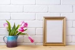 El oro adornó la maqueta del marco con los tulipanes rosados magentas Imágenes de archivo libres de regalías