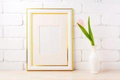 El oro adornó la maqueta del marco con pálido - tulipán rosado en florero Fotos de archivo