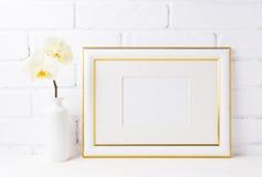 El oro adornó la maqueta del marco del paisaje con la orquídea amarilla suave adentro Fotografía de archivo